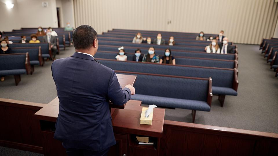 A Latter-day Saint bishop addresses a congregation. The Church attendees are practicing appropriate social distancing during a Sunday worship service. A bishop is a lay leader of a congregation who oversees the well-being of the congregation.