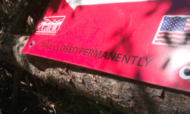 """red sign reads """"Trail Closed Permanently"""""""