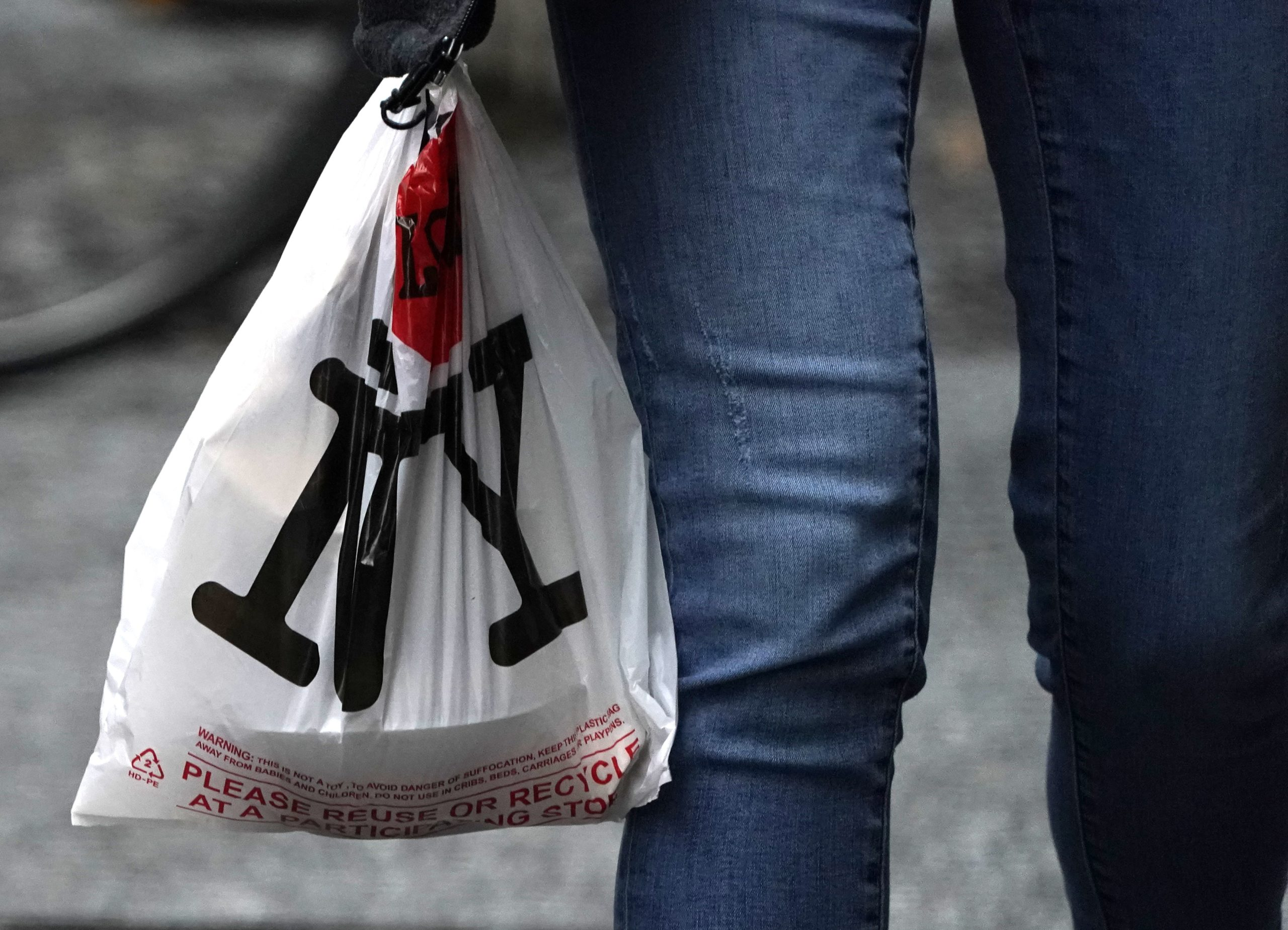 A person with their lunch in a plastic bags walks in midtown in New York on February 28, 2020, ahead of the statewide ban on plastic bags that takes effect March 1. - Consumerist mecca New York targets its throwaway culture this weekend with a ban on single-use plastic bags that has been years in the making and is still rare in America. New Yorkers like to see themselves at the forefront of efforts to save the environment but have become used to receiving groceries in free poly bags often doubled for solidity. On Sunday, that will change when New York becomes only the third US state to outlaw the non-biodegradable carriers blamed for choking rivers, littering neighborhoods and suffocating wildlife. (Photo by TIMOTHY A. CLARY / AFP) (Photo by TIMOTHY A. CLARY/AFP via Getty Images)