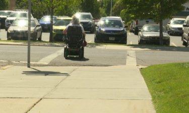woman in wheelchair crosses street