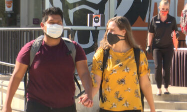 students hold hands wearing face masks