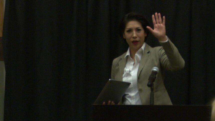 jordan waving to camera from behind podium