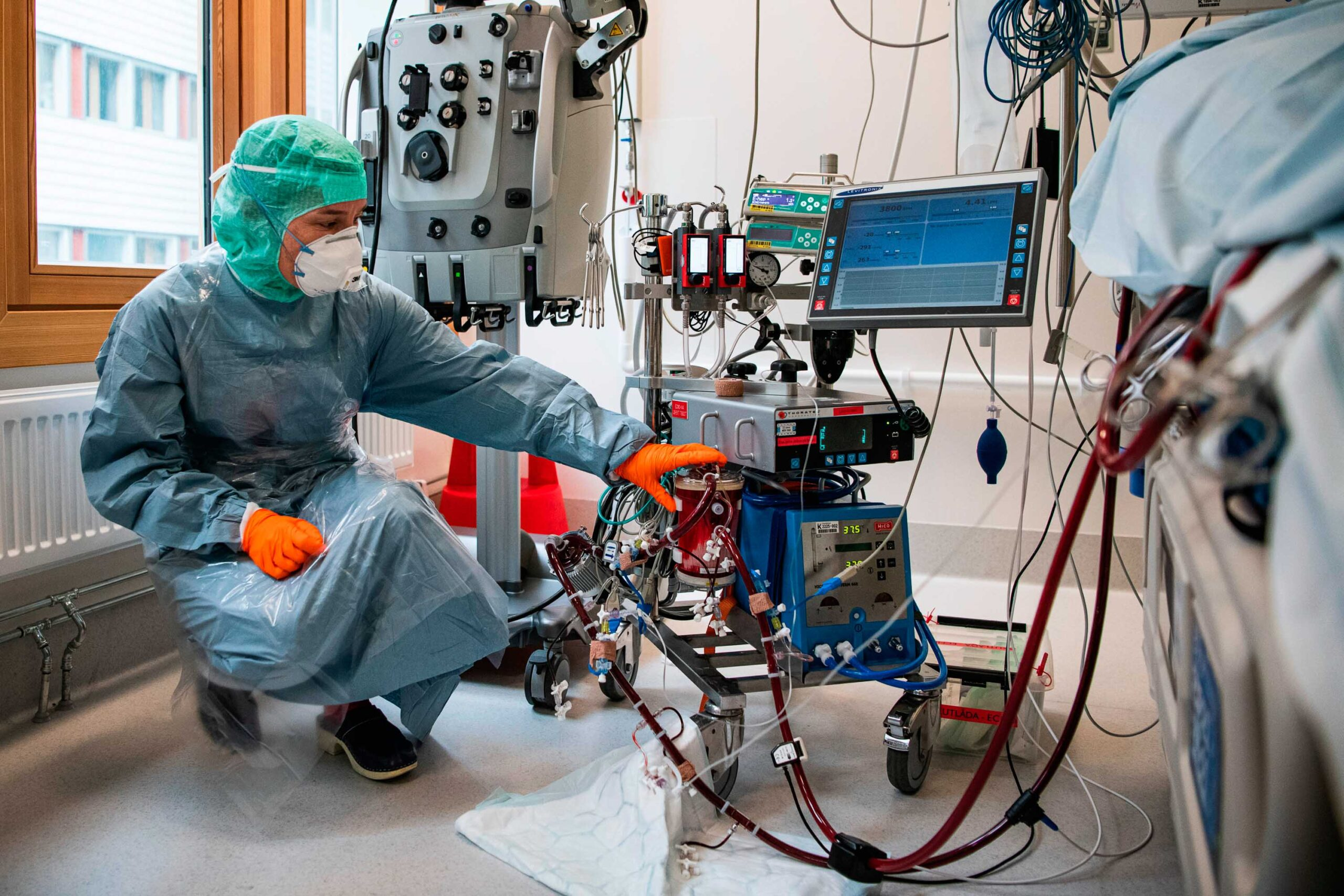 A nurse wearing protective clothing and face mask checks the blood on the ECMO machine as she takes care of a COVID-19 patient at the Extracorporeal Membrane Oxygenation (ECMO) department in the Karolinska hospital in Solna, near Stockholm, Sweden, on April 19, 2020 during the coronavirus COVID-19 pandemic. (Photo by Jonathan NACKSTRAND / AFP) (Photo by JONATHAN NACKSTRAND/AFP via Getty Images)
