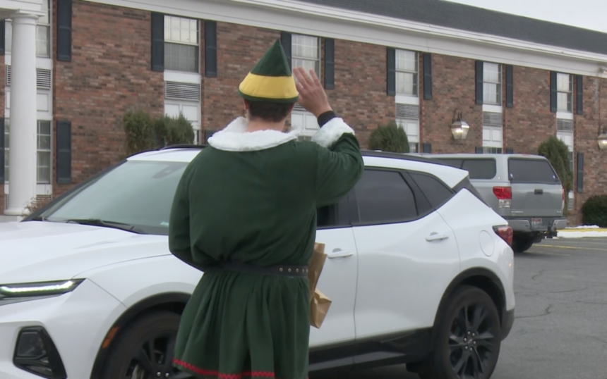 Volunteer Joel Shokes waves at family during Sunday's drive-thru event