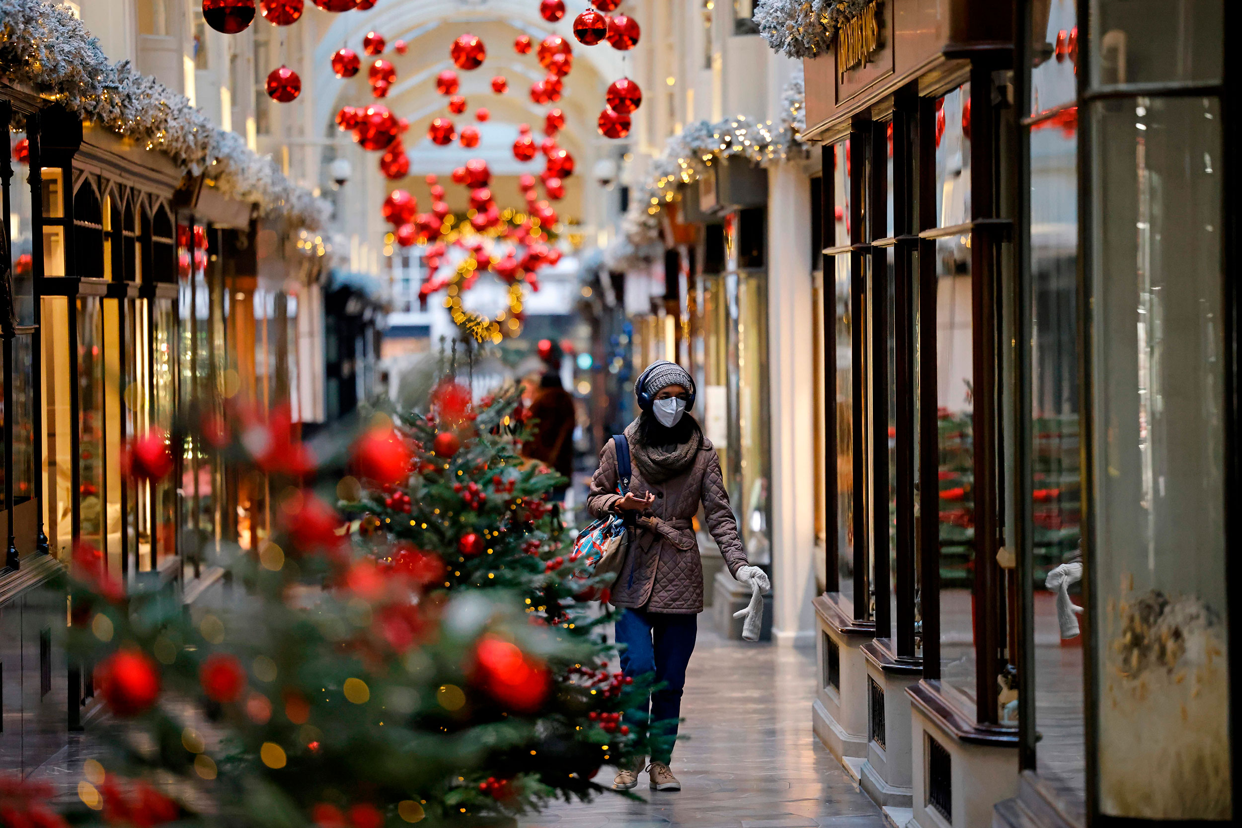 A pedestrian wearing a protective face covering to combat the spread of the coronavirus, walks past Christmas-themed window displays inside Burlington Arcade in central London on November 27, 2020, as life under a second lockdown continues in England. - England will return to a regional tiered system when the national stay-at-home order ends on December 2, and 23.3 million residents in the worst-hit areas are set to enter the