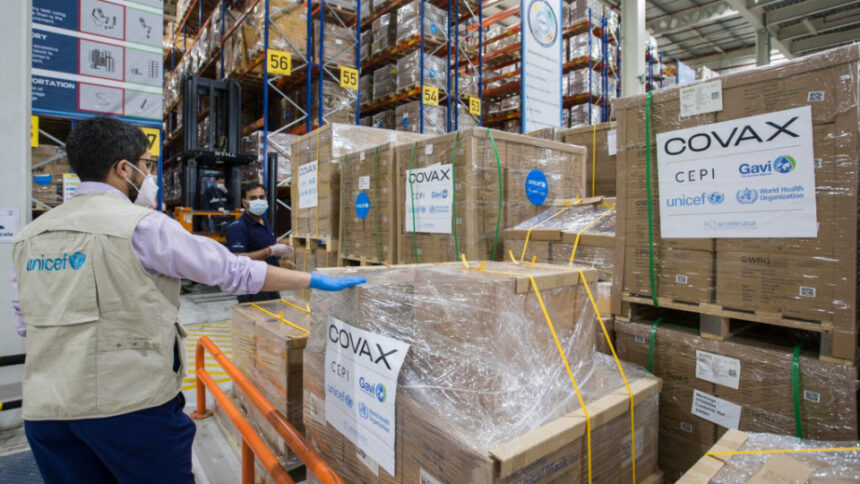 UNICEF staffer Rafik ElOuerchefani inspects pallets of auto-disable syringes and safety boxes at a warehouse in Dubai Logistics City in the United Arab Emirates on February 21, 2021. UNICEF/UN0419491/Pableo