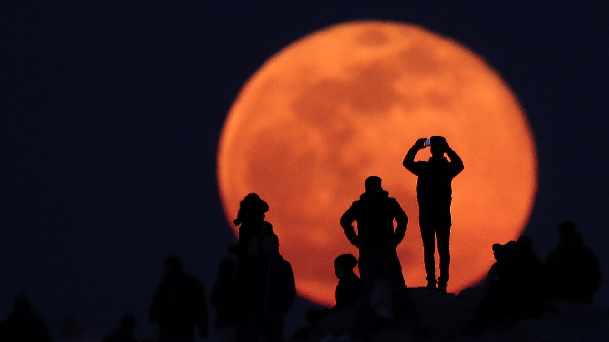 People observe a rising full snow moon rises as they visit the Areios Pagos hill at the archaeological site of the Acropolis in Athens, Greece, February 9, 2020. REUTERS/Alkis Konstantinidis