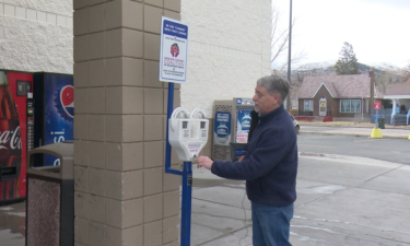 NeighborWorks Pocatello Executive Director Mark Dahlquist empties donation meter outside of Ridley's in Pocatello, ID