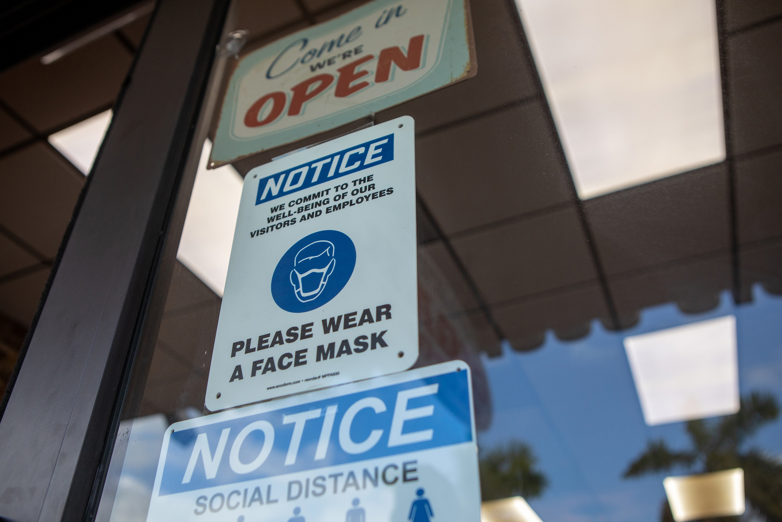 Social-distancing and mask wearing signs on a storefront during the 2020 Presidential election in Miami, Florida, U.S., on Wednesday, Nov. 4, 2020. Trump won two key states where hospitalizations for Covid-19 were among the highest in the U.S. in the past few days, Florida and Ohio, suggesting the jump in cases during the campaign may have done less harm to the Republican camp than expected. Photographer: Jayme Gershen/Bloomberg via Getty Images