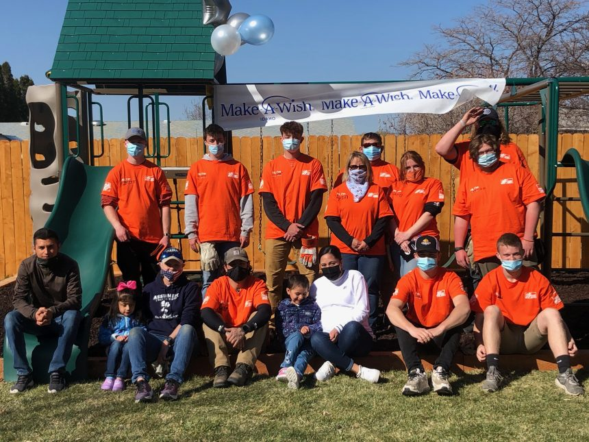 Gutierrez family sits with Home Depot volunteers in front of new playset
