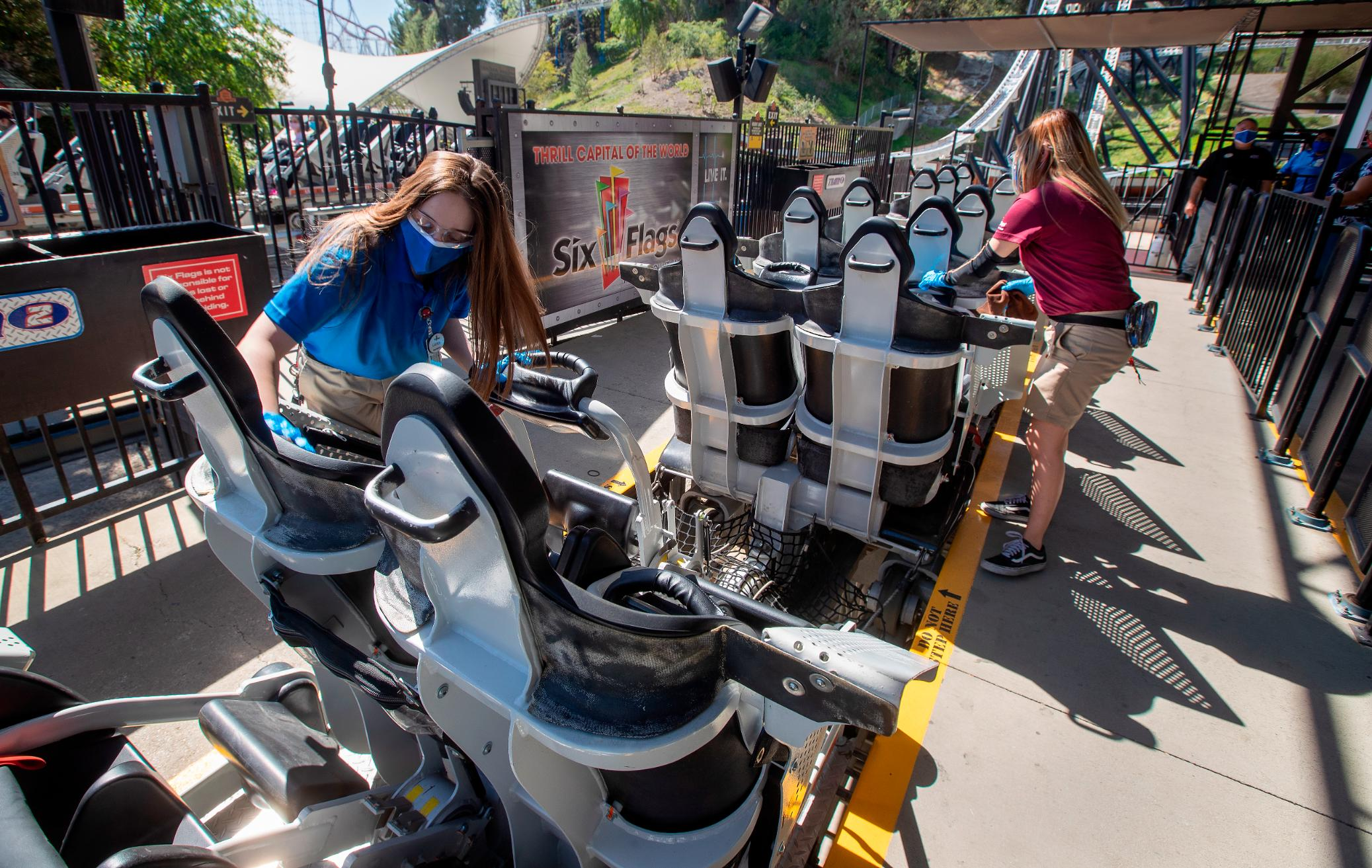 Employees sanitize roller coaster seats at Six Flags Magic Mountain in Valencia, California, on April 2 -- the second day that the park reopened after more than a year of being closed because of the pandemic.