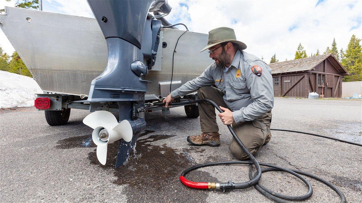 Mike Locatelli, Aquatic Invasive Species Biologist, flushing an engine.