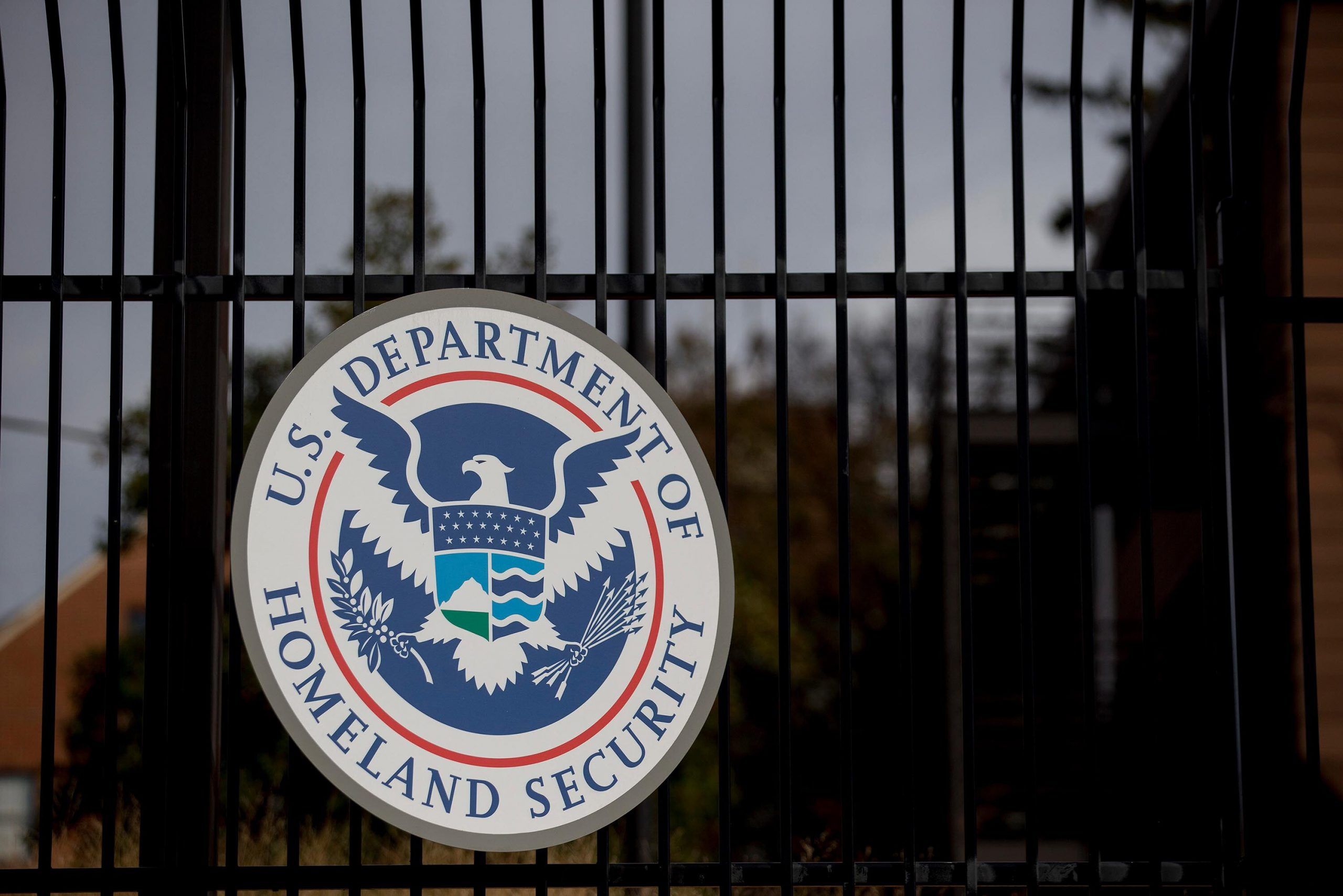 <i>Andrew Harrer/Bloomberg/Getty Images</i><br/>The U.S. Department of Homeland Security (DHS) seal hangs on a fence at the agency's headquarters in Washington
