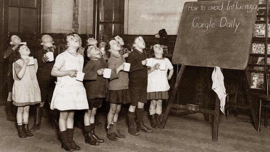 Little schoolchildren gargling their throats as a precaution against the Influenza epidemic. England. Photograph. Around 1935.