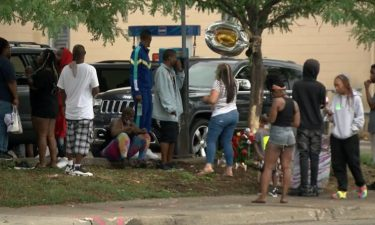 Family and friends gather at the scene of a crash in Minneapolis that took the life of  40-year-old Leneal Frazier.