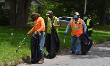 Workers pick up litter along Johnny W. Williams Road in Albany