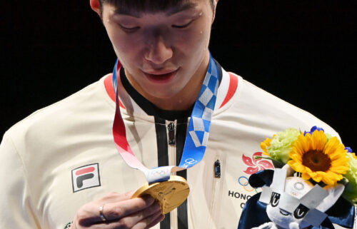 Fencing gold medallist Cheung Ka Long of Hong Kong looks at his medal while on the podium during the medal ceremony for the Men's Individual Foil during the Tokyo 2020 Olympic Games at the Makuhari Messe Hall in Chiba City