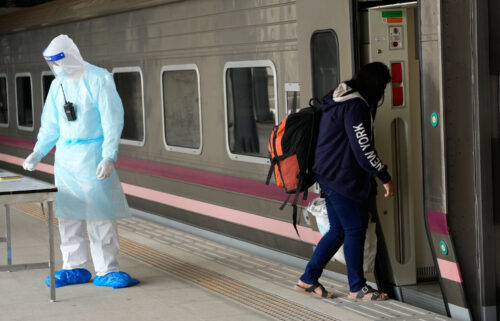 A Covid-19 patient boards a train at Rangsit station on the outskirts of Bangkok to head to her hometown on July 27.