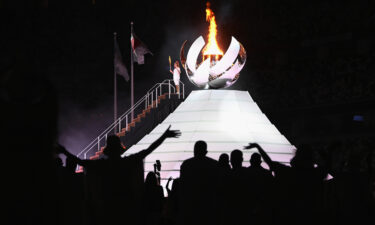 Naomi Osaka of Team Japan lights the Olympic cauldron with the Olympic torch during the opening ceremony of the Tokyo 2020 Olympic Games on Friday