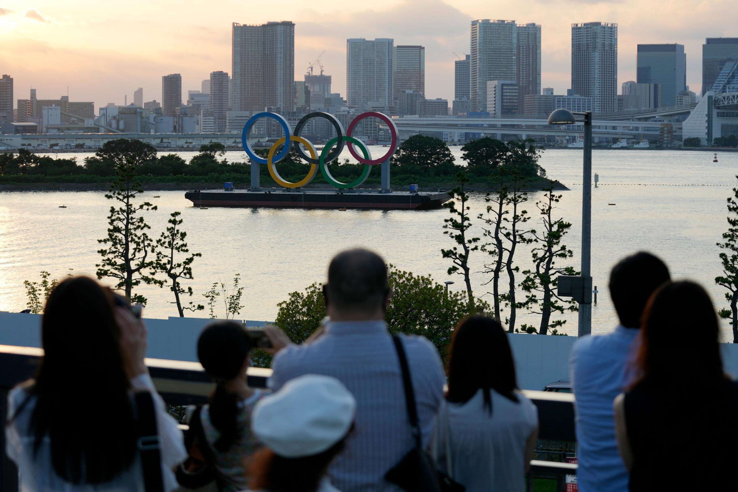 <i>Eugene Hoshiko/AP</i><br/>Visitors look at the Olympic rings floating in the water at Odaiba Marine Park