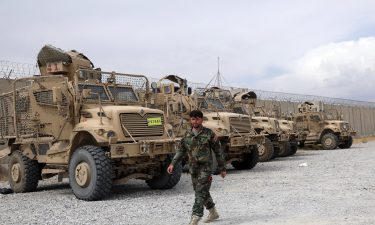 An Afghan army soldier walks past Mine Resistant Ambush Protected vehicles that were left after the American military left Bagram air base