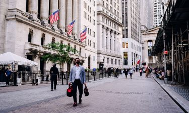 A pedestrian passes by the New York Stock Exchange (NYSE) building in New York