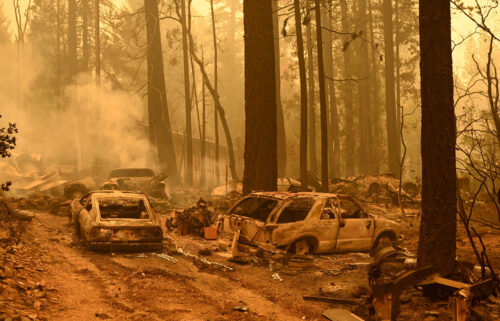 Burned vehicles smolder at a property during the Dixie fire in the Indian Falls area of unincorporated Plumas County.
