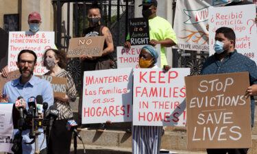 People from a coalition of housing justice groups hold signs protesting evictions during a news conference outside the Statehouse