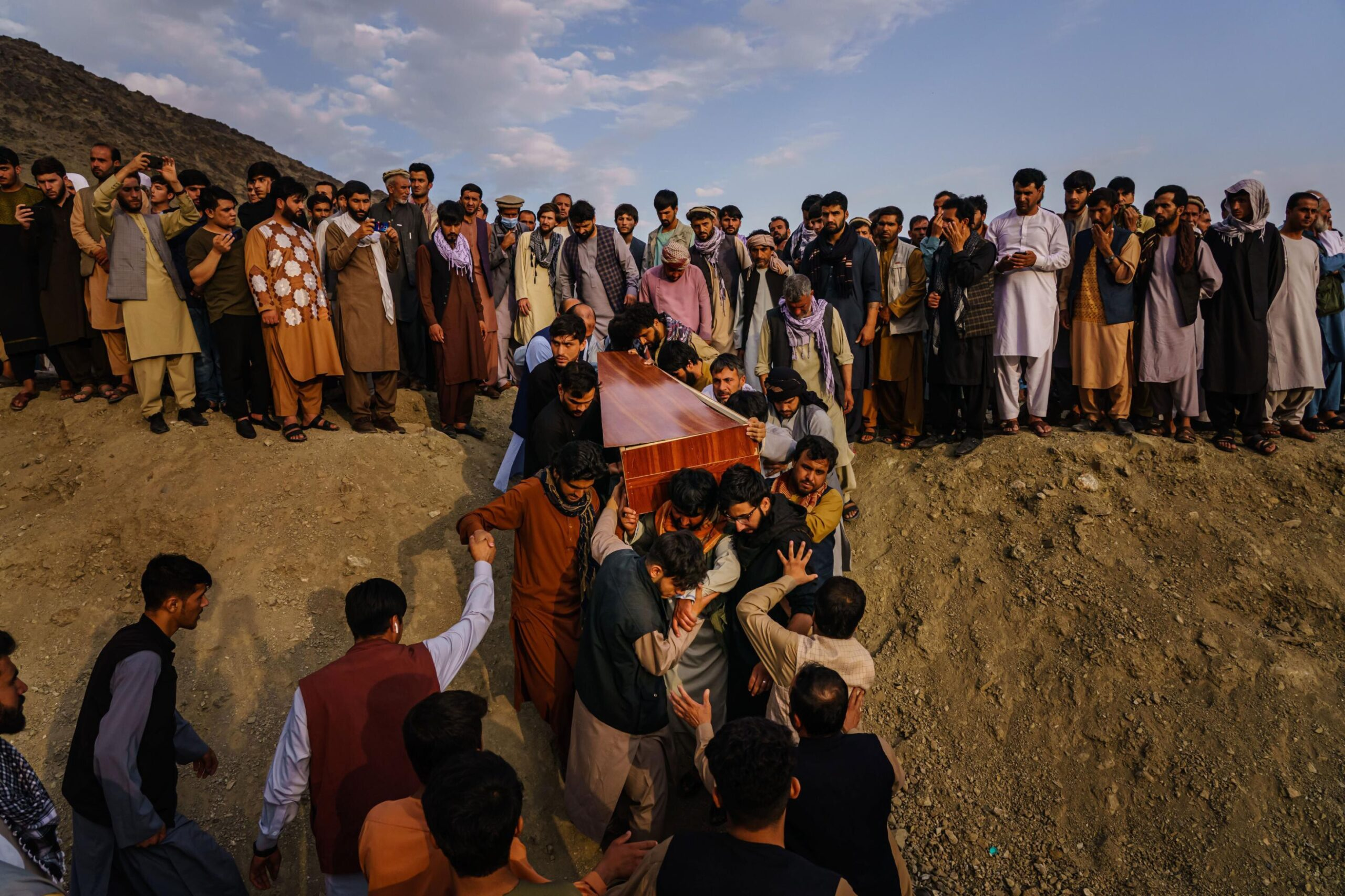 <i>Marcus Yam/The Los Angeles Times/Shutterstock</i><br/>Caskets for the dead are carried towards the gravesite as relatives and friends attend a mass funeral for members of a family that is said to have been killed in a U.S. drone airstrike