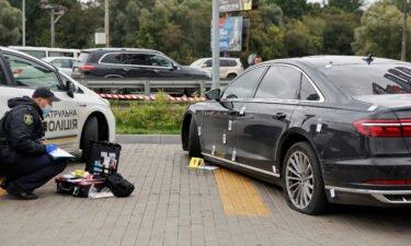 An investigator examines bullet holes in the car of Serhiy Shefir