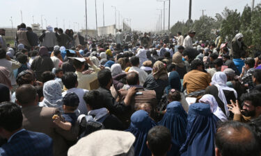 Afghans gather on a roadside near the airport in Kabul on August 20