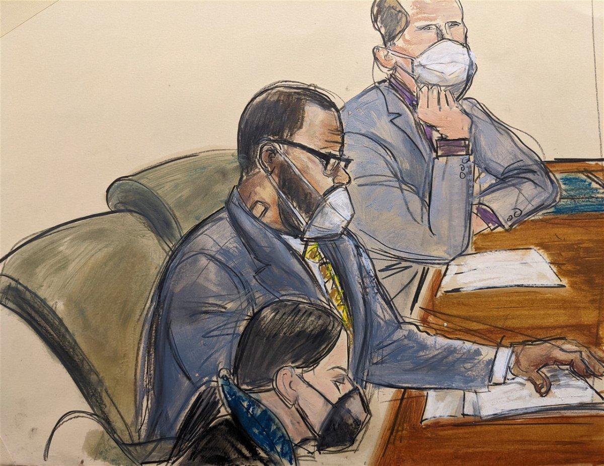<i>Elizabeth Williams/AP</i><br/>R. Kelly sits with his defense attorneys Thomas Farinella
