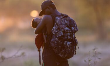 An exhausted Haitian father cradles his son on the Mexican side of the Rio Grande from Del Rio