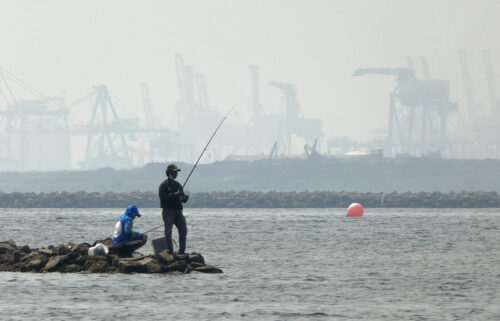 Anglers fish amid thick haze at a coastal area in Jakarta on June 20