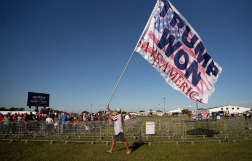 """A man carries a flag that reads """"TRUMP WON"""" before a rally featuring former President Donald Trump on September 25 in Perry"""