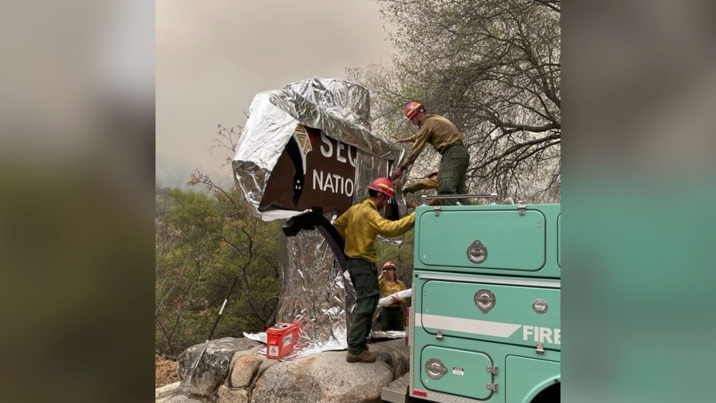<i>From Sequoai & Kings Canyon National Parks/Instagram</i><br/>Firefighters assigned to the KNP Complex Fireprepare the historic Sequoia entrance sign for the possibility of fire in the area by wrapping it with aluminum-based burn-resistant material.