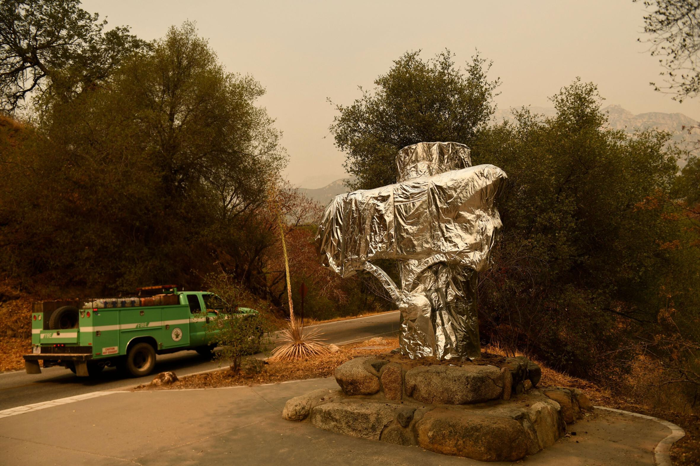 <i>Patrick T. Fallon/AFP/Getty Images</i><br/>A US Forest Service vehicle drives past the Sequoia National Park historic park entrance sign wrapped in fire resistant foil along Generals Highway during a media tour of the KNP Complex fire in the Sequoia National Park near Three Rivers
