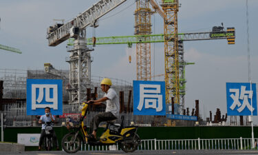 Workers drive their motorbikes in front of the under-construction Guangzhou Evergrande football stadium in Guangzhou