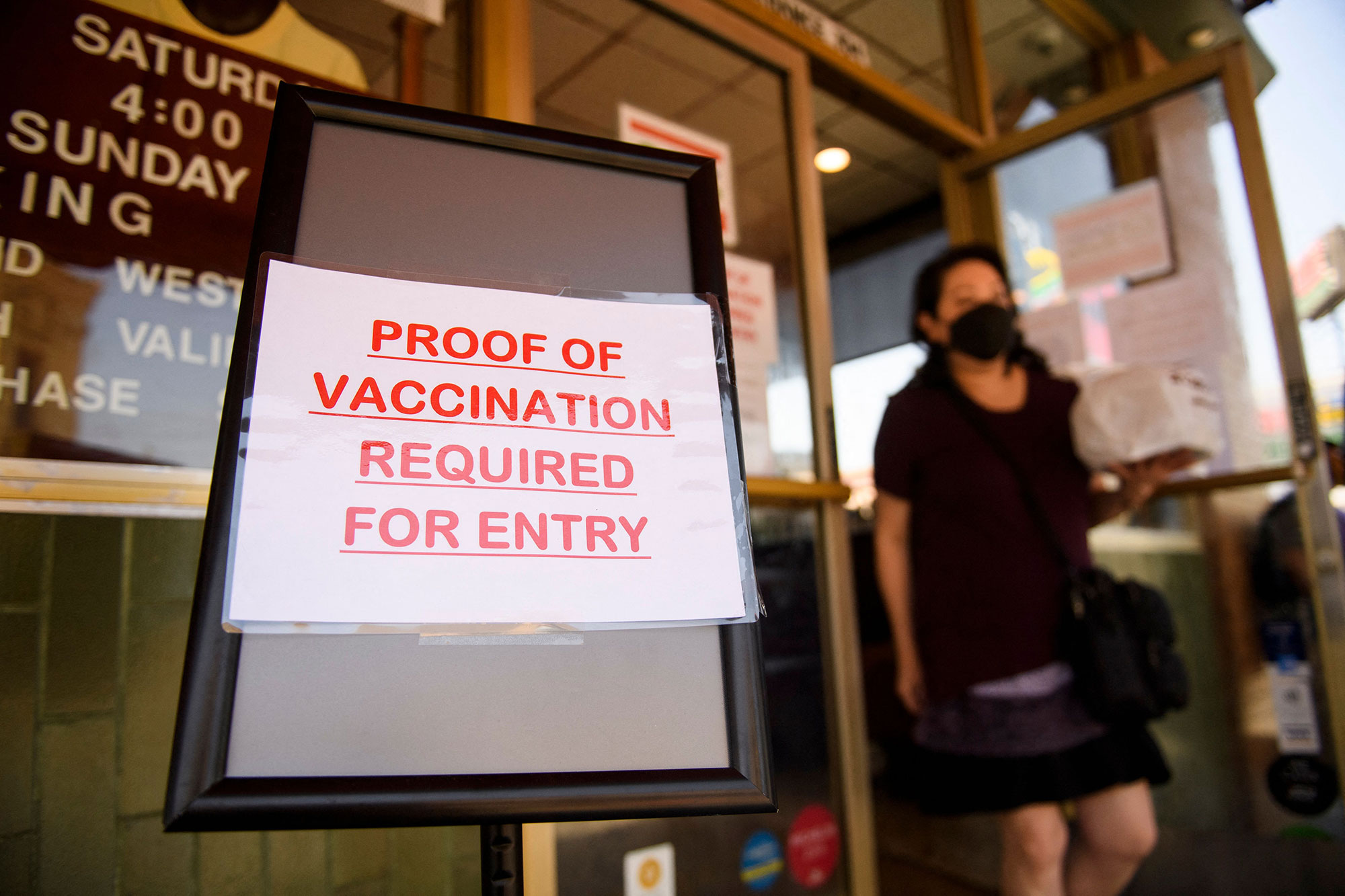 A sign stating proof of a Covid-19 vaccination is required is displayed outside of Langer's Deli in Los Angeles on August 7.