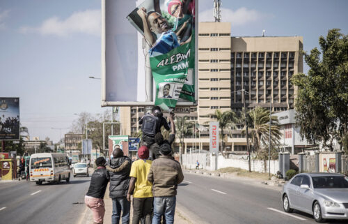 Supporters of Hakainde Hichilema remove a poster of former president Edgar Lungu from a pole in Lusaka