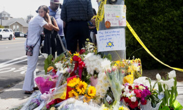 Mourners and well-wishers leave flowers and signs at a makeshift memorial across the street from the Chabad of Poway Synagogue on April 28