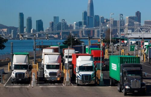 Trucks hauling shipping containers leave the EverPort terminal at the Port of Oakland on October 14