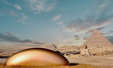 A view of Gisela Colón's spherical metallic sculpture by the Great Pyramids.