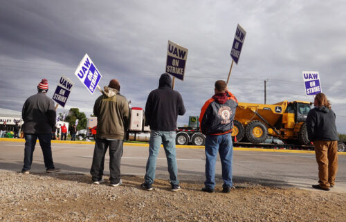 A truck hauls a piece of John Deere equipment from the factory past workers picketing outside of the John Deere Davenport Works facility on October 15 in Davenport