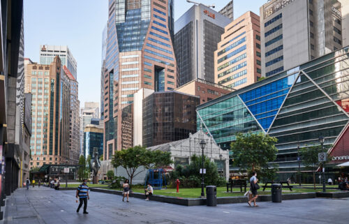 Singapore will extend its Covid-19 restrictions for another month after the city-state reported 18 new deaths from the disease. Pedestrians are seen here passing through a near empty Raffles Place in the central business district of Singapore