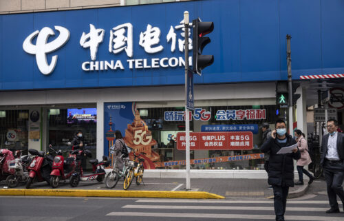 Washington is barring a major Chinese state-owned telecommunications firm from operating in the United States over national security concerns. Pedestrians are seen walking past a Telecom Corp. store in Shanghai