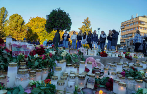 Flowers and candles are placed at a makeshift memorial for the victims of the Kongsberg attack on Stortorvet in Kongsberg
