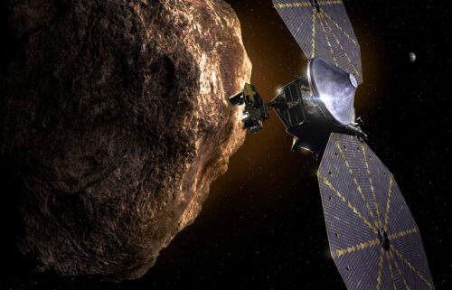 This illustration shows the Lucy spacecraft passing one of the Trojan asteroids near Jupiter.