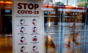 A sign reminds festivalgoers to monitor themselves for possible coronavirus symptoms in the entrance of the Princess of Wales Theatre on day one of the 2021 Toronto International Film Festival