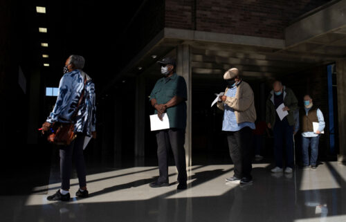 People wait in line with their paperwork to receive their coronavirus booster vaccination during a Pfizer-BioNTech vaccination clinic in Southfield